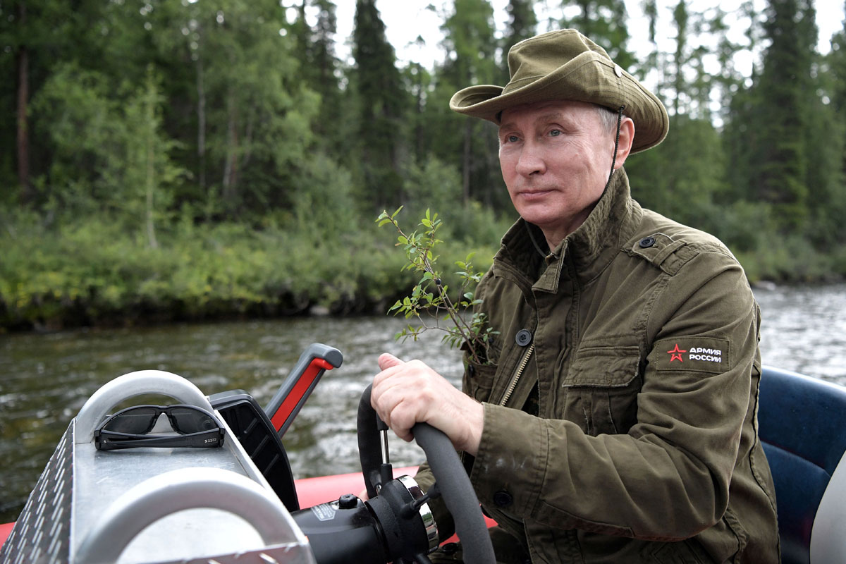 Russian President Vladimir Putin controls a boat during the hunting and fishing trip which took place on August 1-3 in the republic of Tyva in southern Siberia