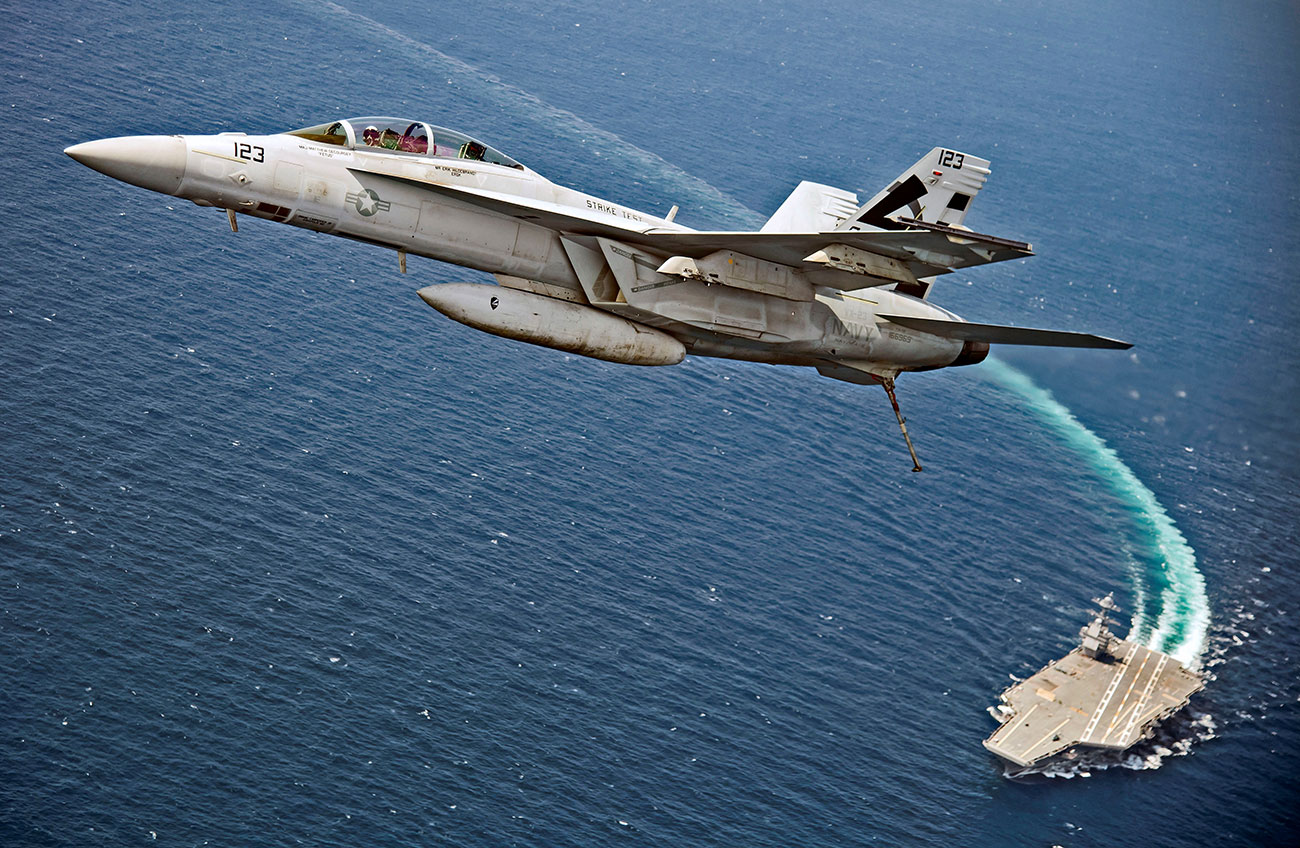 An F/A-18F Super Hornet jet flies over the USS Gerald R. Ford as the U.S. Navy aircraft carrier tests its new launch and flight arrest systems