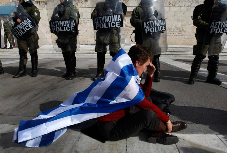 An anti-austerity protester draped with a Greek flag sits in front of police guarding parliament in Athens February 11, 2012 during a demonstration on the second day of a 48-hour strike by Greek workers unions.