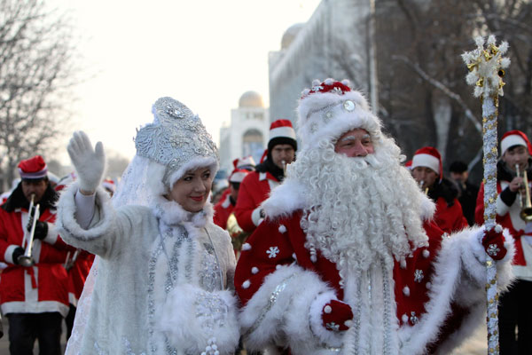 """<p>A man who is dressed up as Father Frost, the local equivalent of Santa Claus, and his """"granddaughter"""" Snegurochka (Snow Maiden) greet passers-by during a New Year's Day parade in Bishkek.</p>"""