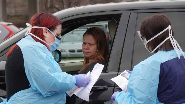 Healthcare workers with ChristianaCare test people with symptoms of the coronavirus in a drive-thru in the parking lot of Chase