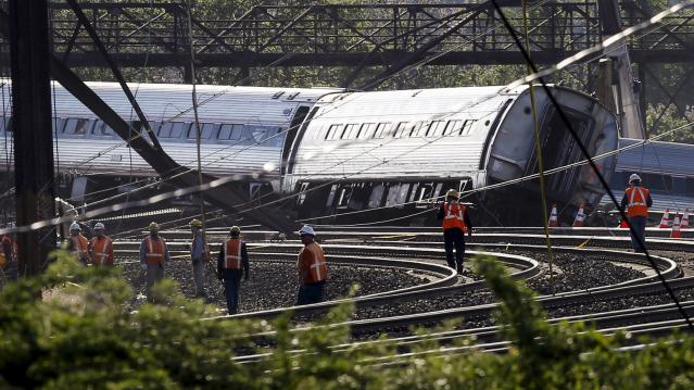 Officials survey the site of a derailed Amtrak train in Philadelphia, Pennsylvania