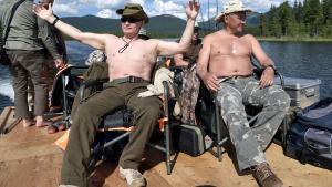 Russian President Vladimir Putin and Defence Minister Sergei Shoigu rest after fishing during the hunting and fishing trip which took place on August 1-3 in the republic of Tyva in southern Siberia