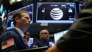 Traders work on the floor near the post where telecoms company AT&T is traded at the NYSE