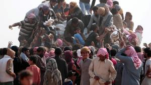 Iraqi refugees that fled violence in Mosul and internally displaced Syrians who fled Islamic State controlled areas in Deir al-Zor, gather near the Iraqi border