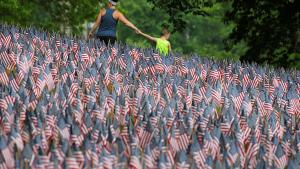 Visitors walk past a field of United States flags displayed by the Massachusetts Military Heroes Fund on the Boston Common in Boston