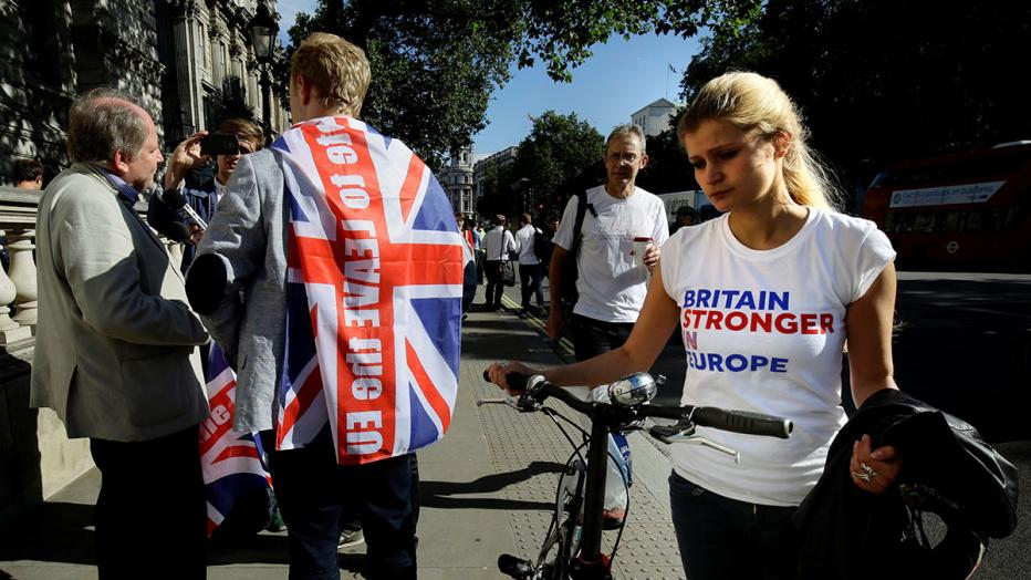 A vote remain supporter walks past a vote leave supporter outside Downing Street in London
