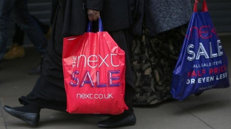 Shoppers carry bags advertising a sale on Oxford Street in London, Britain