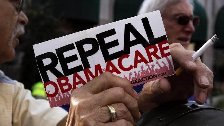 "A small group of demonstrators stand outside of of a hotel before former South Carolina Senator Jim DeMint, president of the The Heritage Foundation, speaks at a ""Defund Obamacare Tour"" rally in Indianapolis, Indiana, U.S.  August 26, 2013.  REUTERS/Nate"