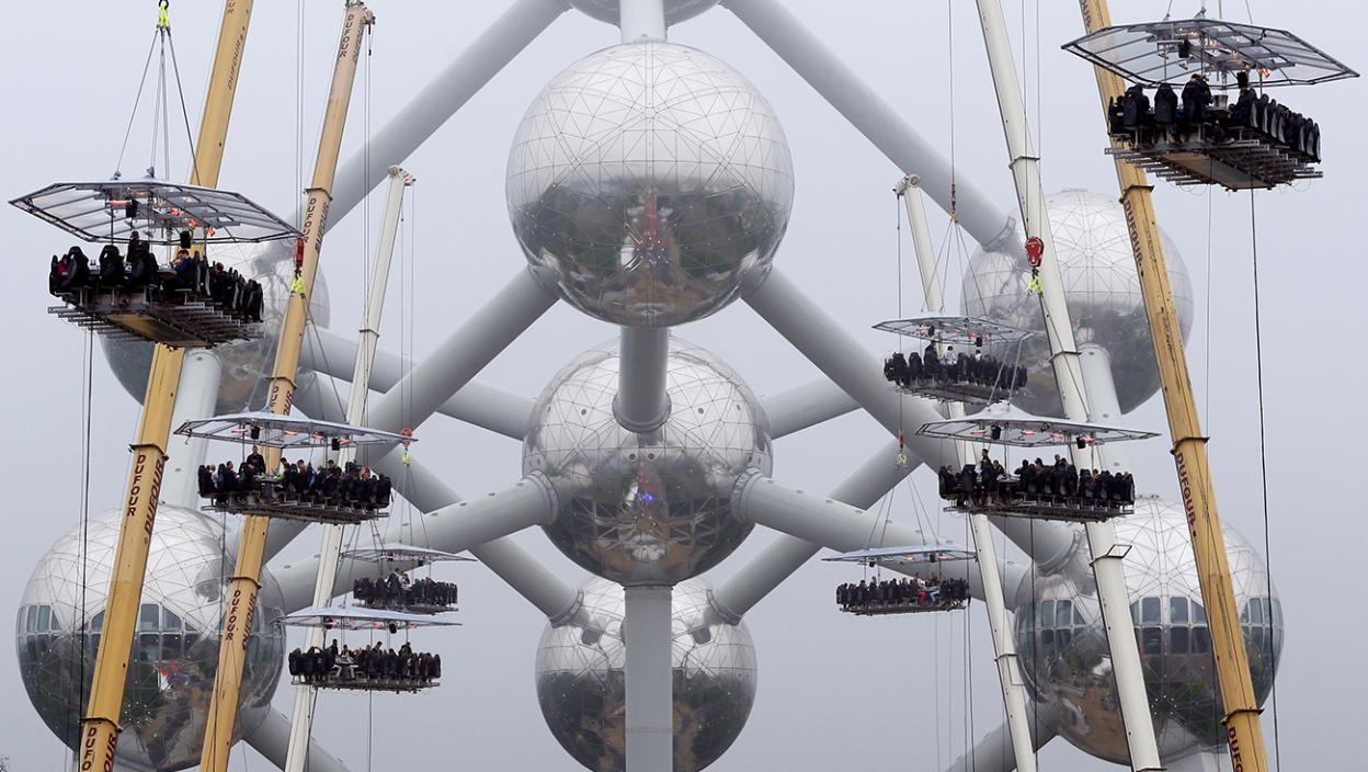 """Guests sit at tables suspended from cranes at a height of 40 metres in front of the Atomium, as part of the 10th anniversary of the event known as """"Dinner in the Sky"""", in Brussels"""