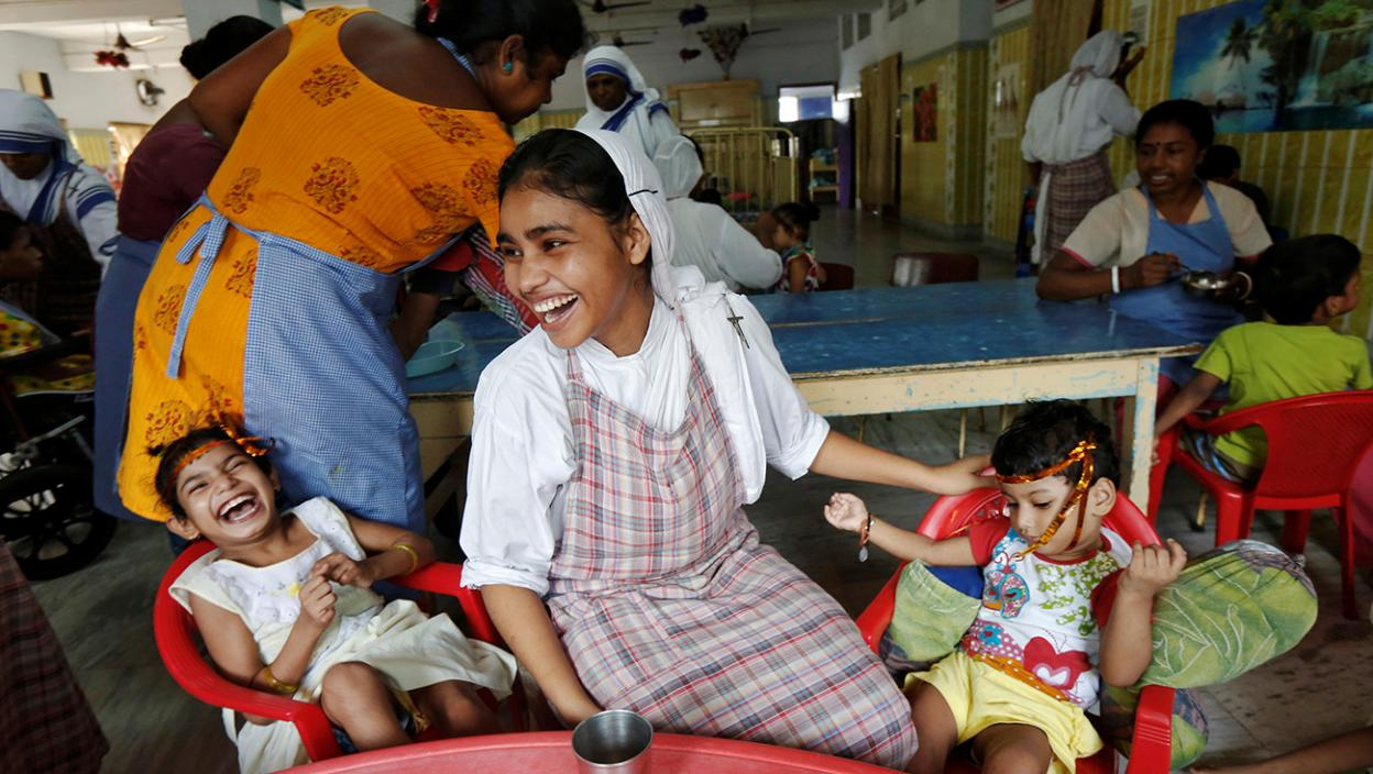 A nun belonging to the global Missionaries of Charity reacts as she interacts with children at the Nirmala Shishu Bhavan in Kolkata