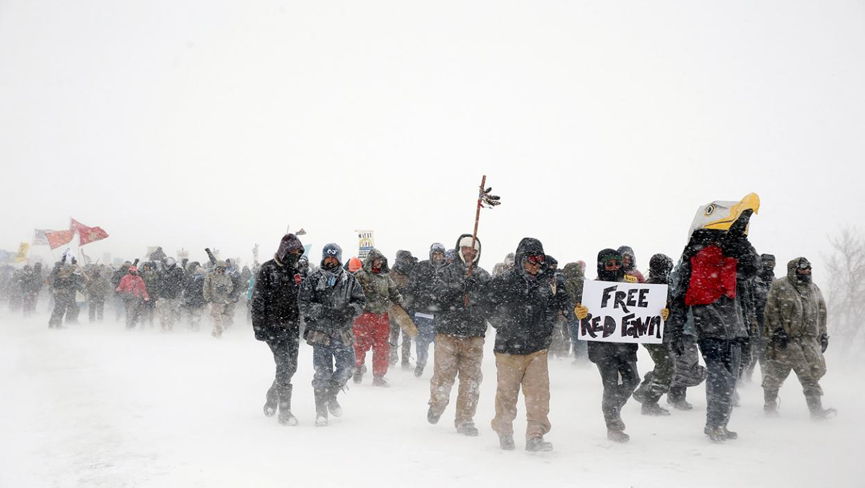 """Veterans join activists in a march just outside the Oceti Sakowin camp during a snow fall as """"water protectors"""" continue to demonstrate against plans to pass the Dakota Access pipeline adjacent to the Standing Rock Indian Reservation, near Cannon Ball,"""