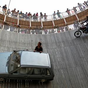 "Stunt performers ride a motorcycle and a car on the walls of the ""Well of Death"" at the Magh Mela fair in Allahabad"