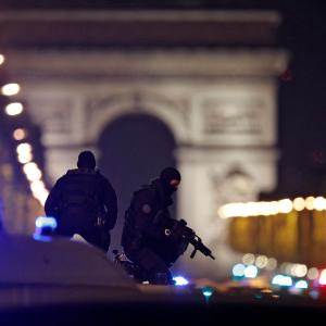 Masked police stand on top of their vehicle on the Champs Elysees Avenue after a shooting incident in Paris