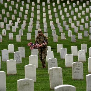 Flags are placed on headstones for Memorial Day at Arlington Cemetery