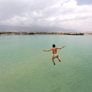 An Afghan boy jumps for a swim at Qargha lake in Kabul
