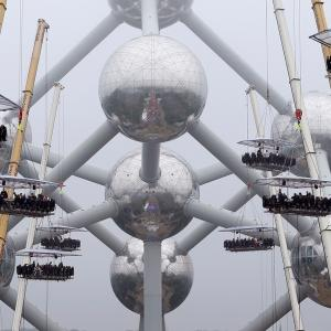 "Guests sit at tables suspended from cranes at a height of 40 metres in front of the Atomium, as part of the 10th anniversary of the event known as ""Dinner in the Sky"", in Brussels"