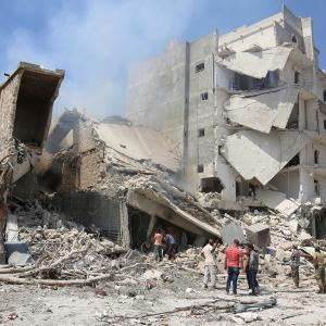 Men inspect a damaged site after double airstrikes on the rebel held Bab al-Nairab neighborhood of Aleppo