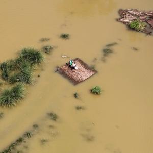 People stand on a partially submerged house as they wait to receive food parcels being distributed by a Indian Air Force helicopter on the outskirts of Allahabad