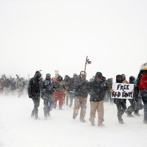 "Veterans join activists in a march just outside the Oceti Sakowin camp during a snow fall as ""water protectors"" continue to demonstrate against plans to pass the Dakota Access pipeline adjacent to the Standing Rock Indian Reservation, near Cannon Ball,"