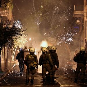 Fireworks explode next to riot police during clashes following an anniversary rally marking the 2008 police shooting of 15-year-old student, Alexandros Grigoropoulos, in Athens