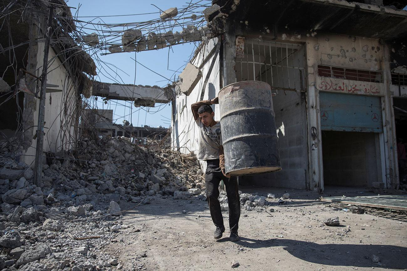 A man carries a barrel as people collect steel from a destroyed building in Mosul