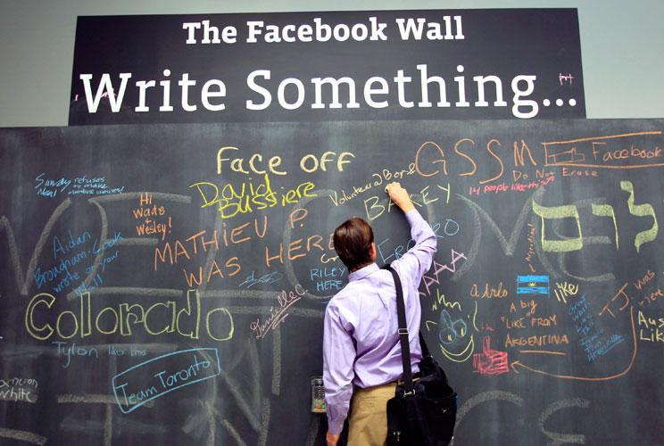 An employee writes a note on the message board at the new headquarters of Facebook in Menlo Park, California on January 11, 2012. The 57-acre campus, which formerly housed Sun Microsystems, features open work spaces for nearly 2,000 employees on the one m