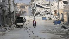 Birds fly near men riding a motorcycle through a damaged neighbourhood in the northern Syrian town of al-Bab