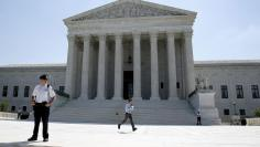 A television news assistant runs to his co-workers with printed copies of U.S. Supreme Court decisions at the court building in Washington