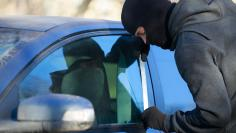 A thief using a metal rod to unlock the front door of a car