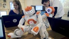 "Visitors and staff work on computers next to humanoid robots ""Nao"" at the workshop of Aldebaran Robotics company during its opening week in Issy-Les-Moulineaux near Paris"