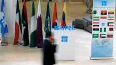 A man walks past an OPEC logo ahead of an informal meeting between members of the Organization of the Petroleum Exporting Countries (OPEC) in Algiers