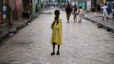A child stands on a street, after Hurricane Matthew passes Cite-Soleil in Port-au-Prince