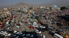Vehicles drive at a junction in downtown Kabul