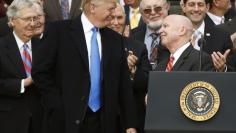 President Donald Trump and House Ways and Means Committee Chairman Kevin Brady smile at each other after the U.S. Congress passed sweeping tax overhaul legislation, on the South Lawn of the White House in Washington