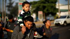 Father and son walk in a caravan of migrants en route to U.S. in San Salvador