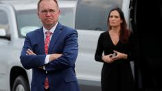 White Chief of Staff Mick Mulvaney and Stephanie Grisham, spokesperson for first lady Melania Trump, wait by a van after their arrival in Orlando