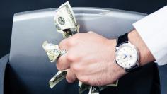 Businessman hands throwing US dollar bills in trash bin