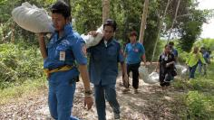Rescue workers carry body bags with remains retrieved from a mass grave in Thailand's southern Songkhla province