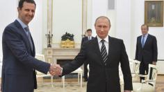 File photo of Russian President Putin shaking hands with Syrian President Assad during a meeting at the Kremlin in Moscow