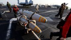An aviation ordnanceman transports bombs onboard the USS Dwight D. Eisenhower CVN 69 carrier in Arabia Gulf