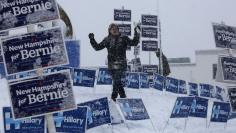 A worker walks amongst election signs in the snow in Manchester