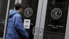 A customer reads a sign posted on the door of a Chipotle Mexican Grill in New York