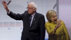 Democratic U.S. presidential candidates Senator Bernie Sanders and former Secretary of State Hillary Clinton arrive on stage before the start of the PBS NewsHour Democratic presidential candidates debate in Milwaukee