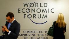 Attendees use their mobile device during the annual meeting 2016 of the WEF in Davos