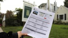 A woman holds a piece of paper advertising a home for sale in Santa Monica