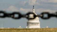 U.S. Capitol is photographed behind a chain fence in Washington