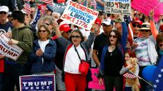 Women carry signs with pro-Trump rally participants  during the Southern California Make America Great Again march in support of President Trump, the military and first responders at Bolsa Chica State Beach in Huntington Beach, California