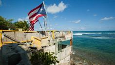 Puerto Rico and U.S. flags flutter on a building that once belonged to a restaurant in San Juan