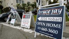 Signs advertising open houses for real estate sale are seen in Los Angeles